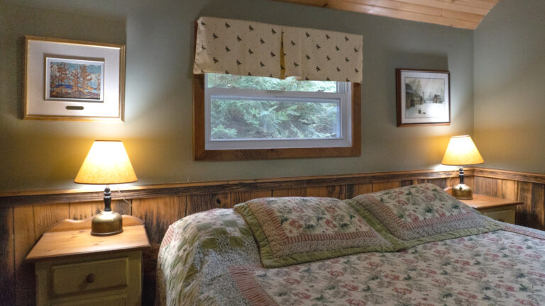 large bed with a pink and green floral quilt flanked by two wooden side tables and lit lamps in a green and wood paneled room with a small window overlooking the forest