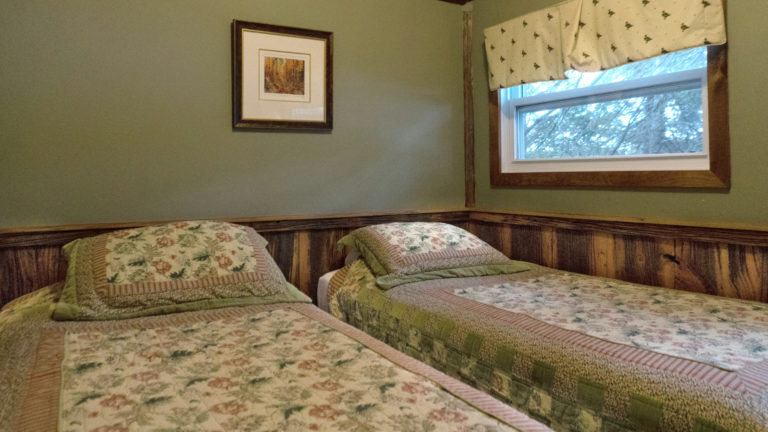 two twin beds with pink and green floral quilts in a green and wood paneled room with a small window overlooking the forest
