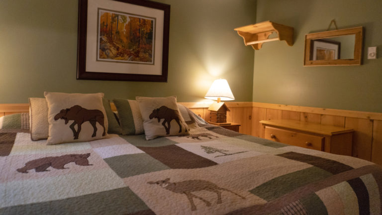 large bed with green and beigh quilt insude a green and wood paneled room with an antique dresser and lit table lamp