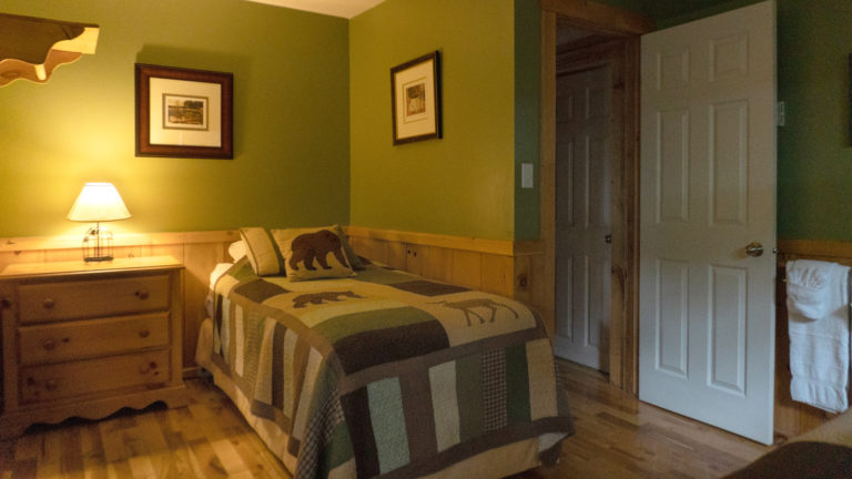 twin bed with green and beigh quilt insude a green and wood paneled room with an antique dresser and lit table lamp