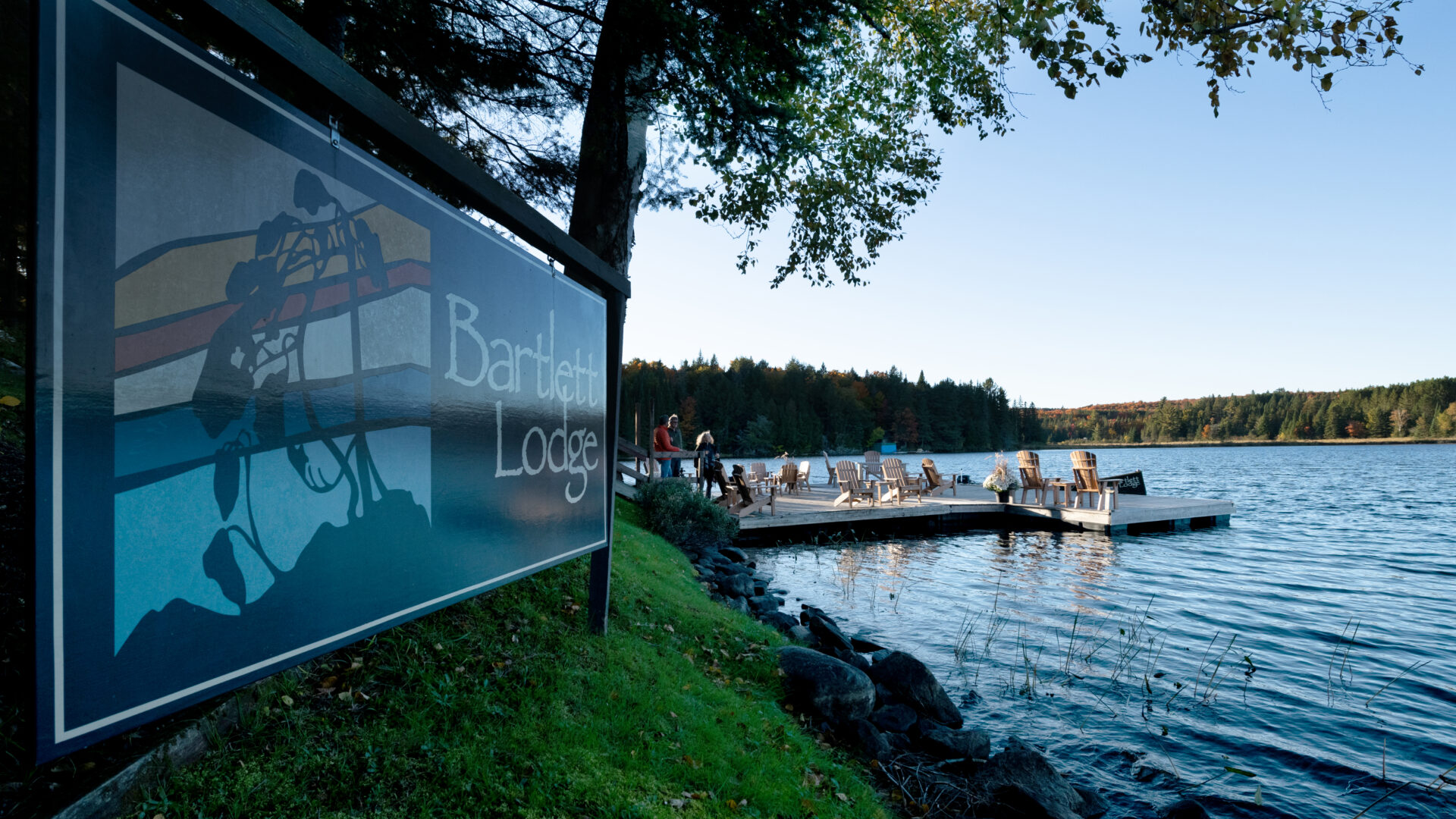 Bartlett Lodge sign on a grassy hill beside Cache Lake and dock with wooden Muskoka chairs