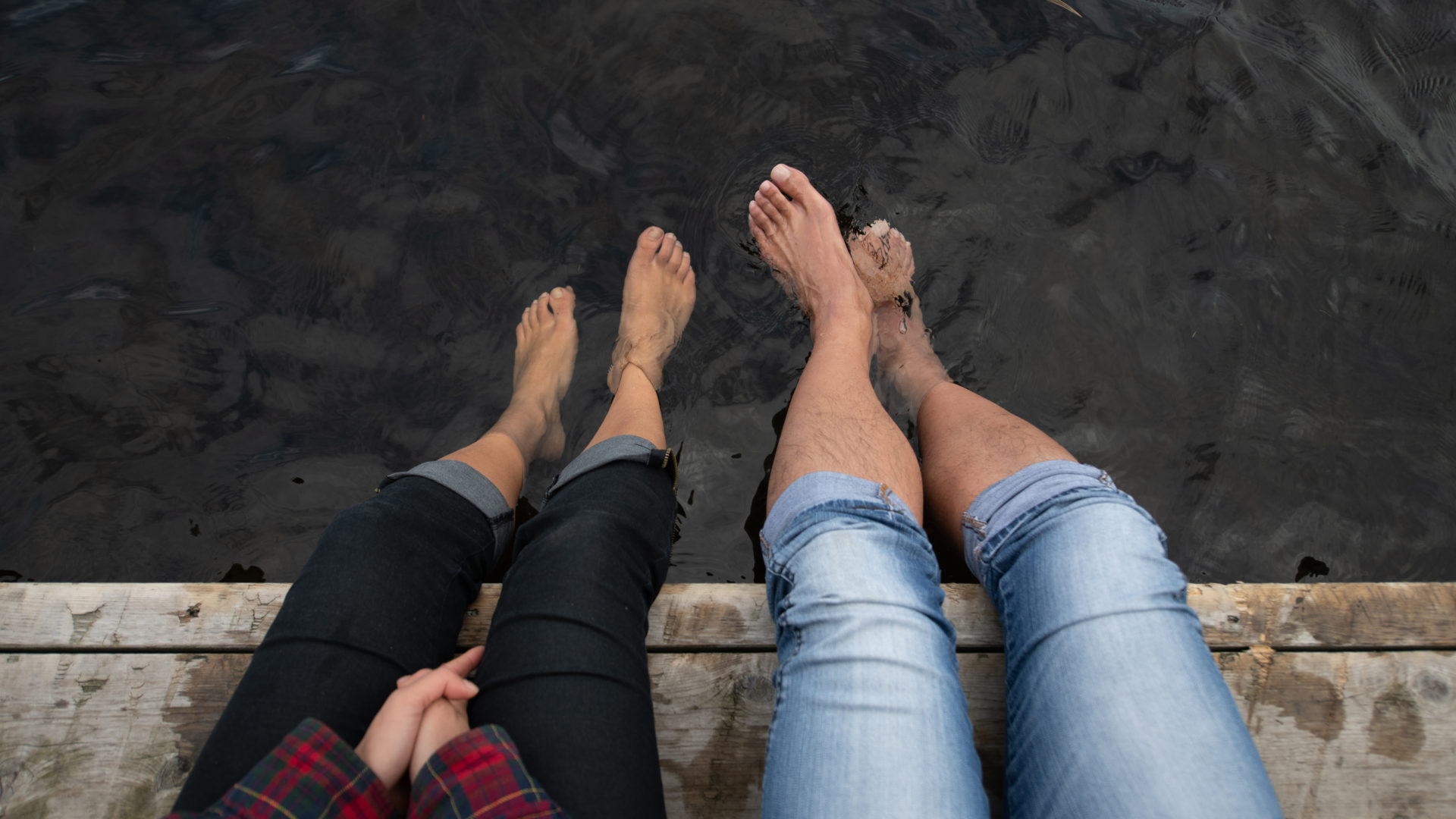 legs from the knees down of a man and woman sitting on a dock with their jeans rolled up and feet dangling in the water
