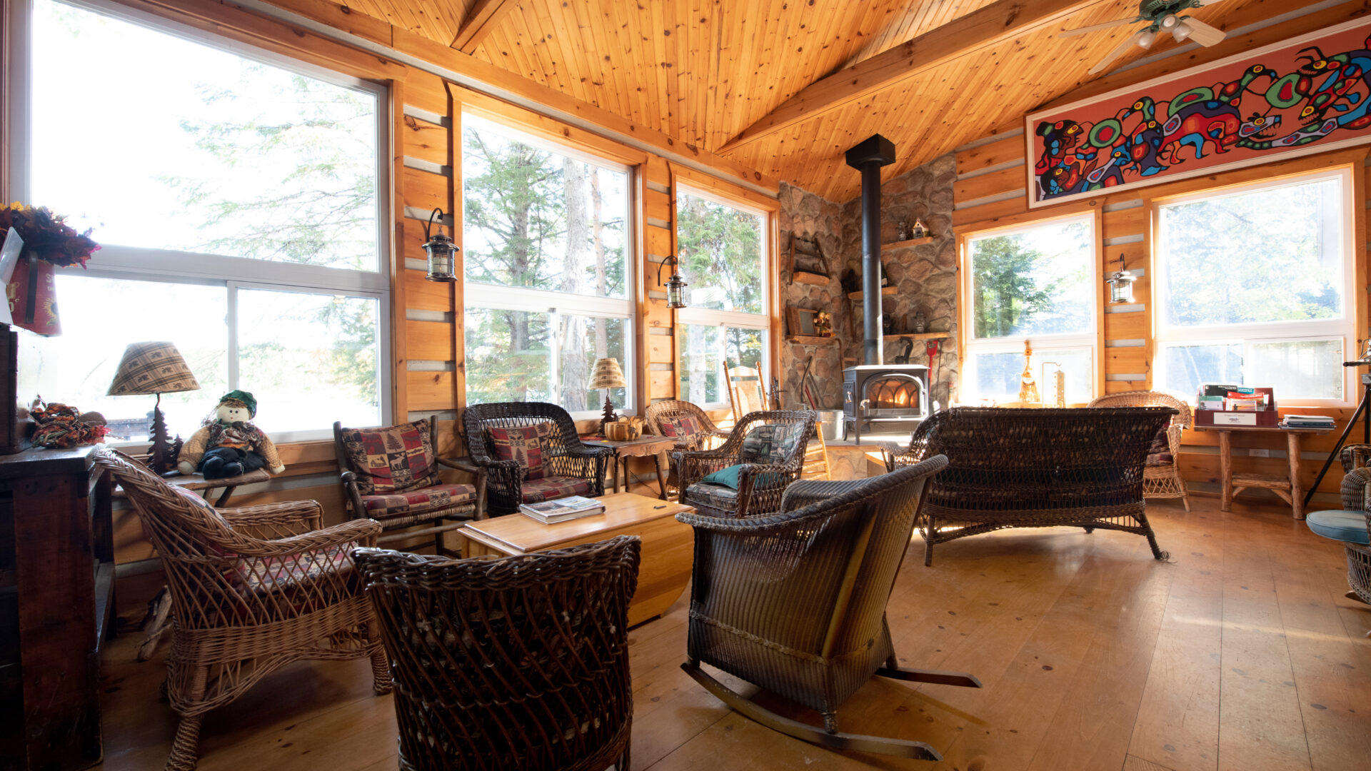 sun-filled room with pine paneling on the walls filled with wicker lounge furniture, a wood burning stove and indigenous Canadian artwork