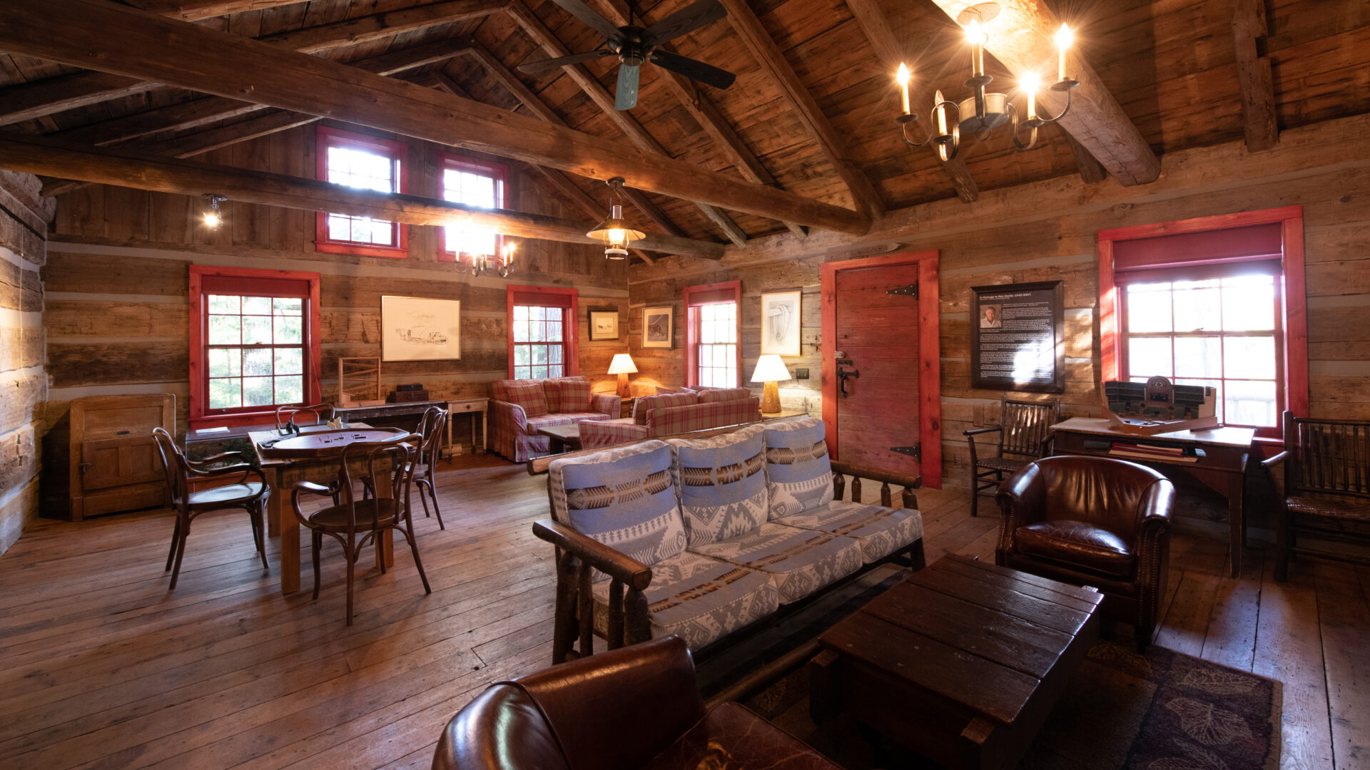 Interior of large log cabin with two seating areas and an antique wood dining table and chairs