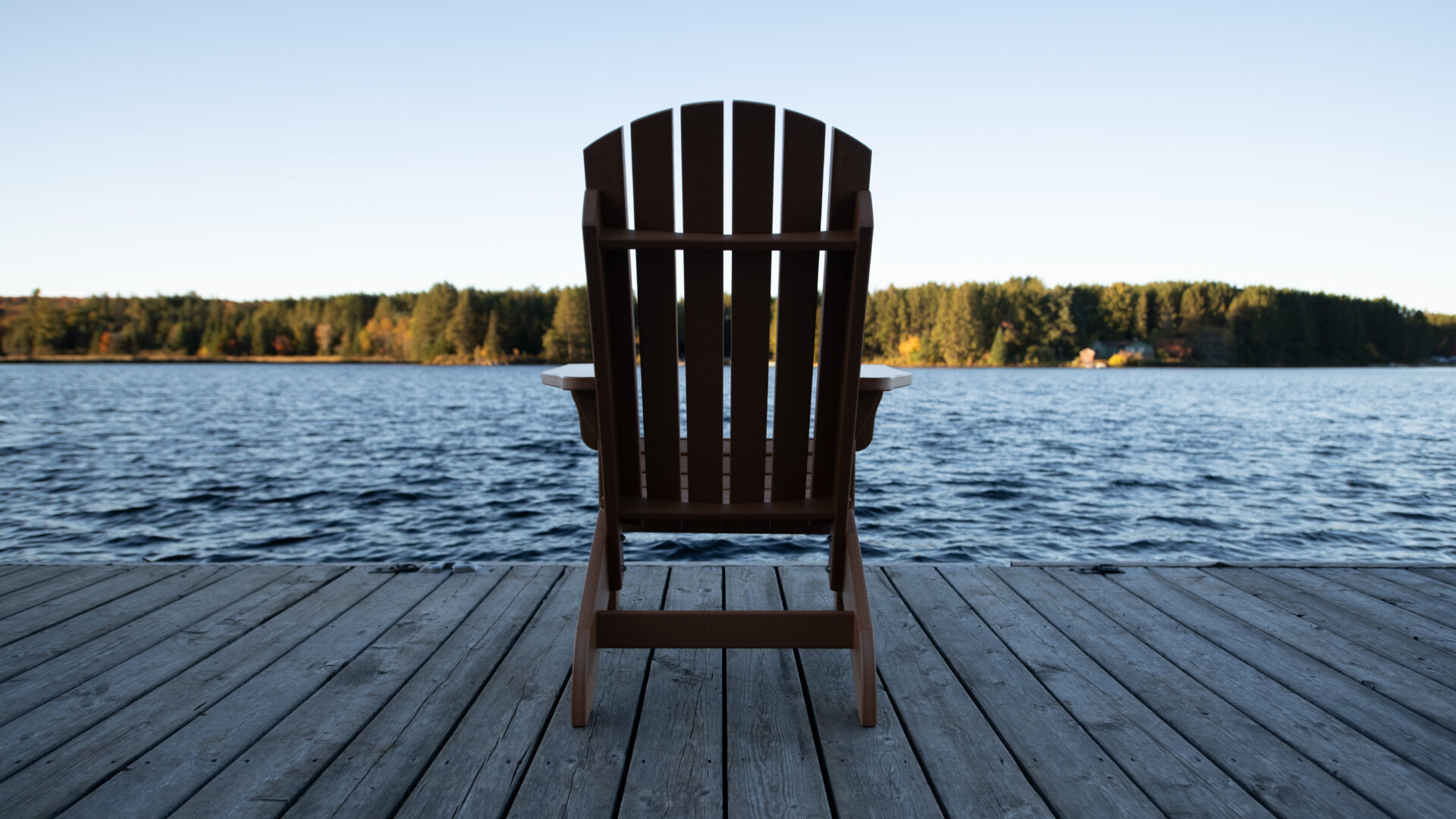 silhouette of the back of a single Muskoka chair on the dock in front of Cache Lake