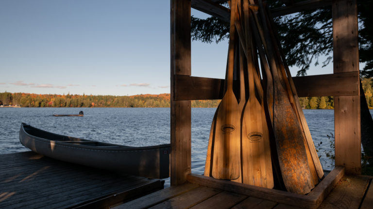group of canoe paddles leaning on a wooden fence next to a lake with canoe in the late afternoon