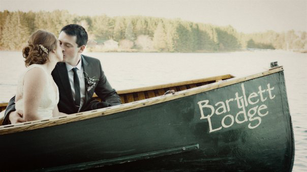bride and groom kissing in a green Bartlett Lodge canoe on Cache Lake