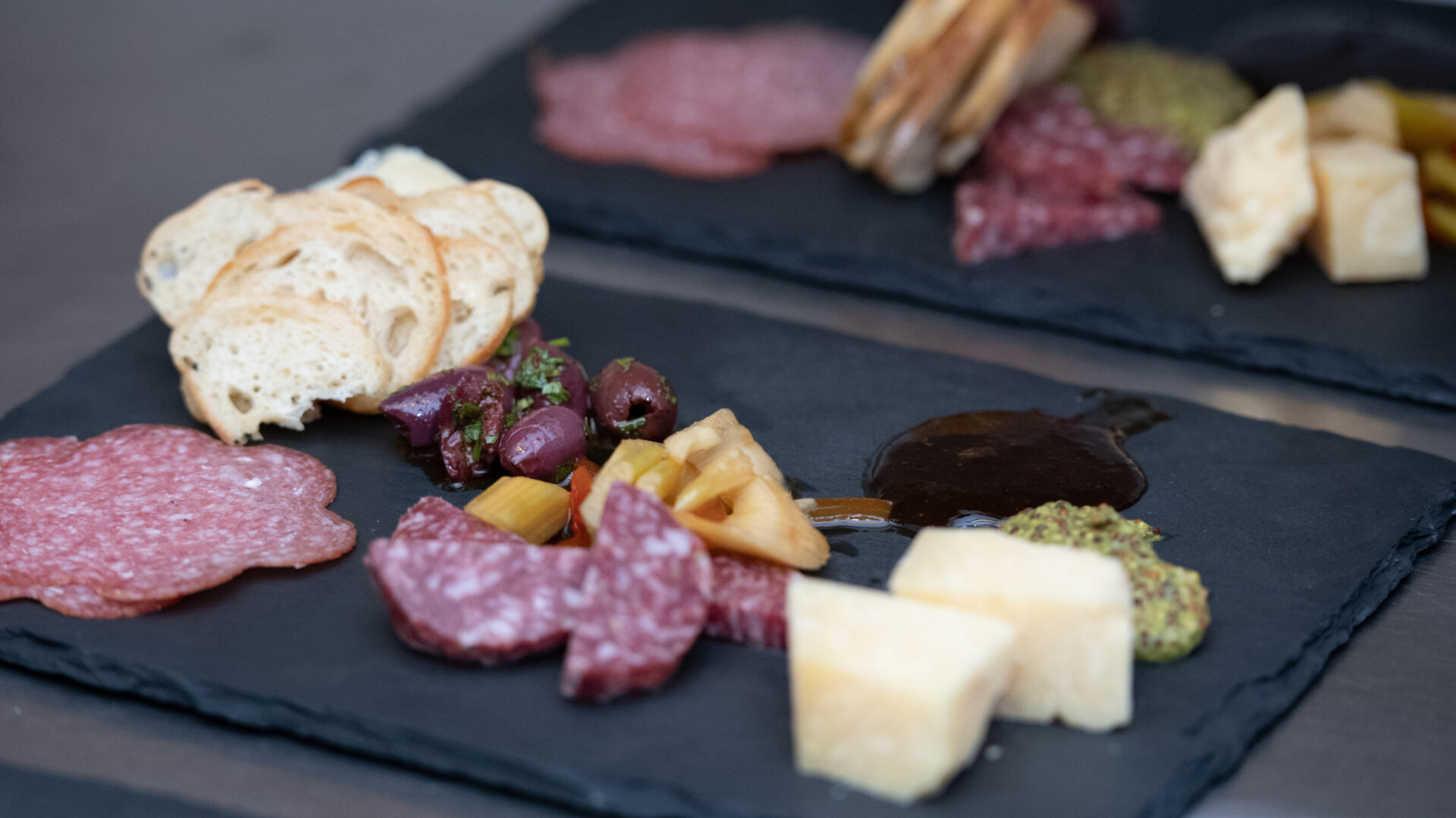 close up of sliced baguette, salami, mustard, olives and cheese on a black slate serving platter