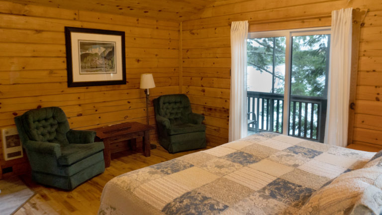 two green upholstered chairs and the end of a bed with a blue and white patch work quilt inside a log cabin