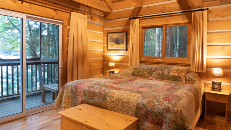 large bed with a patch work quile in a log cabin with a pine chest at the foot of the bed, two side tables with lit lamps and a view of the lake through sliding glass doors