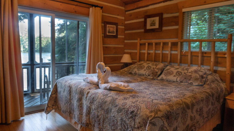 large bed with a neutral floral quilt, log headboard and two towels folded like swans in a loving embrace in a log cabin with a view of the lake through glass paneled sliding doors