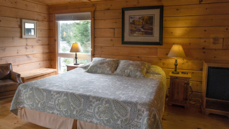 large bed with blue paisley quilt flanked by pine night tables and lit lamps. Out the winder a view of pine trees and a lake can be seen