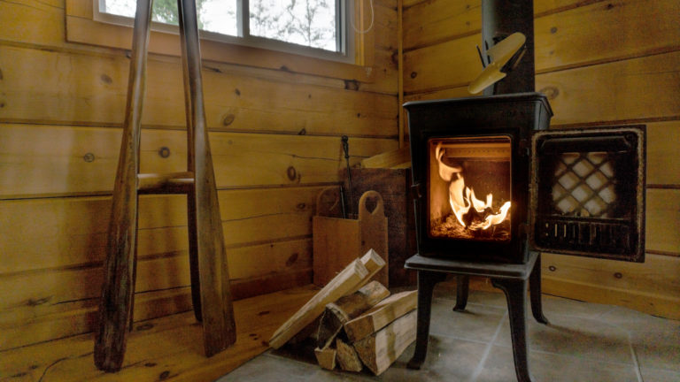 lit standalone cast iron fireplace with door open inside a log cabin with a pile of chopped wood sitting beside it