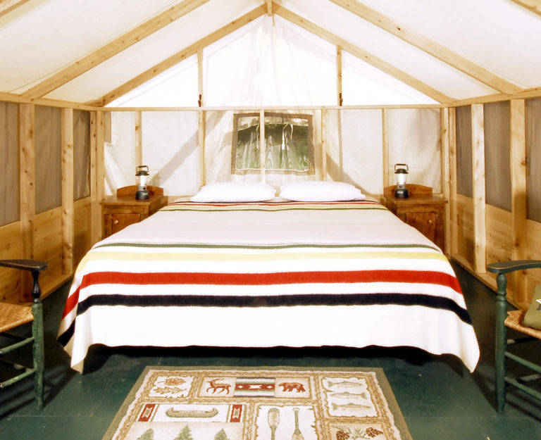 inside of a wood and canvas tent with two green wooden chairs, two antique wooden sidetables with lanterns and a bed covered in a Hudson's Bay point blanket