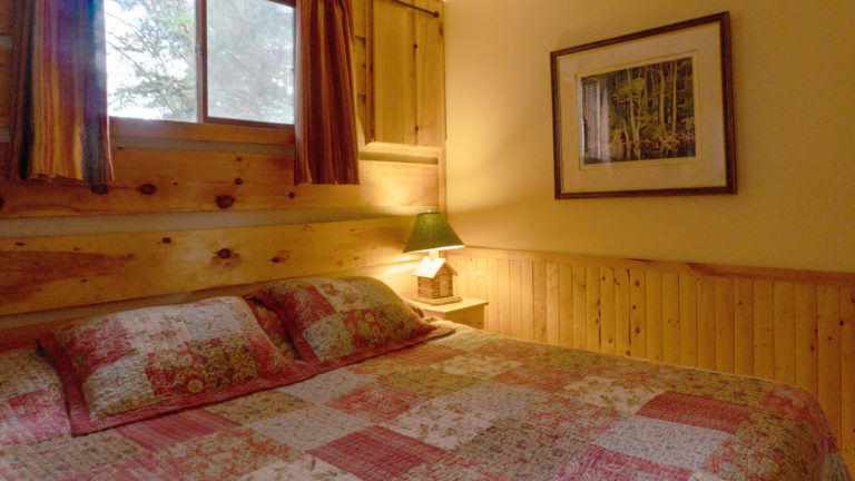 large bed with a pink and white patch work quilt in a wood paneled and yellow room with a lit lamp that's shaped like a log cabin