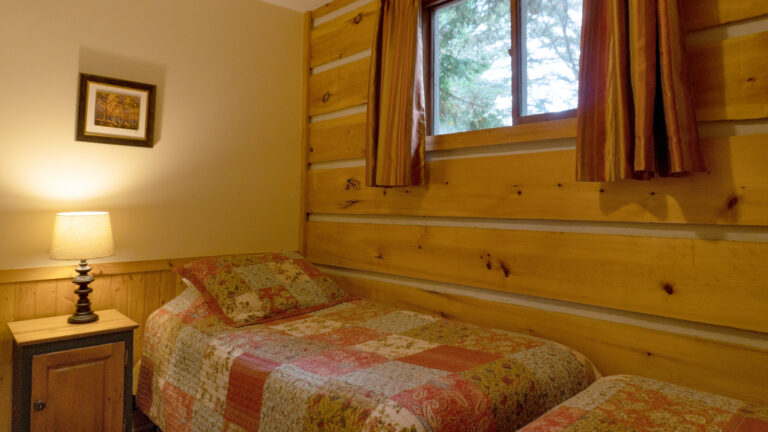 twin bed with a pink and white patch work quilt in a wood paneled and yellow room with a lit lamp