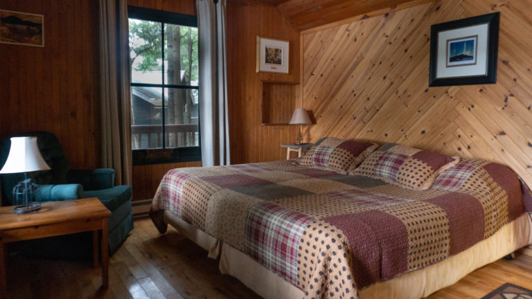 large bed with a brown and red quilt inside a wood paneled room with a blue easy chair, side table and lamp