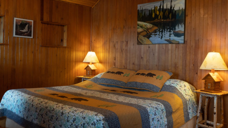 large bed with a bear-themed quit in a wood paneled bedroom with birch side tables, two lit lamps and group of seven artwork hanging over the bed