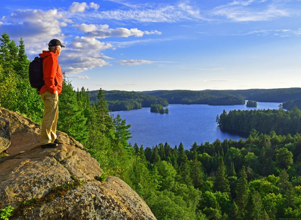 Man standing on a rocking outcrop above a beautiful Algonquin park lake