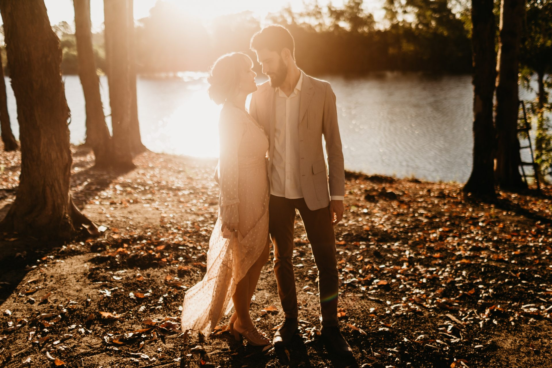 Newlyweds standing in front of a lake in a beautiful late fall setting